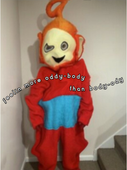 Someone wearing an unofficial teletubbies costume of the character Po, who is a large round red alien looking type creature with big ears and a circular antennae coming out the top of it's head and a blue square on it's tummy. They are standing at the bottom of a set of stairs in a white hallway. The costume is saggy and mishapen and the face is slightly menacing with wide eyes and a smile. The image has been edited to accentuate the sagginess with a slight swirling all over the costume. White text with a black background in two arches says 'feelin more oddy-body than body-ody'