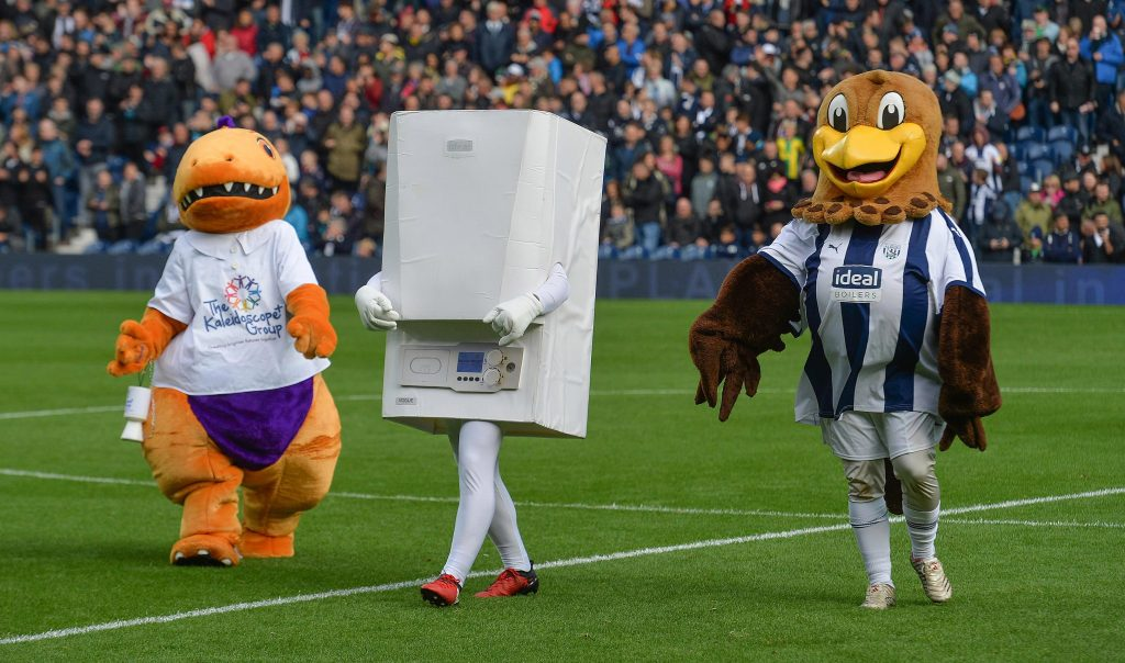 A green football field with busy stalls filled with fans in the background. In the forefront is three mascots walking together, on the left is an orange dinosoar with a white shirt on holding a charity collection tin, in the middle is a white boiler with white arms and legs and red football trainers, on the right is an eagle with a white and navy blue striped football kit on.
