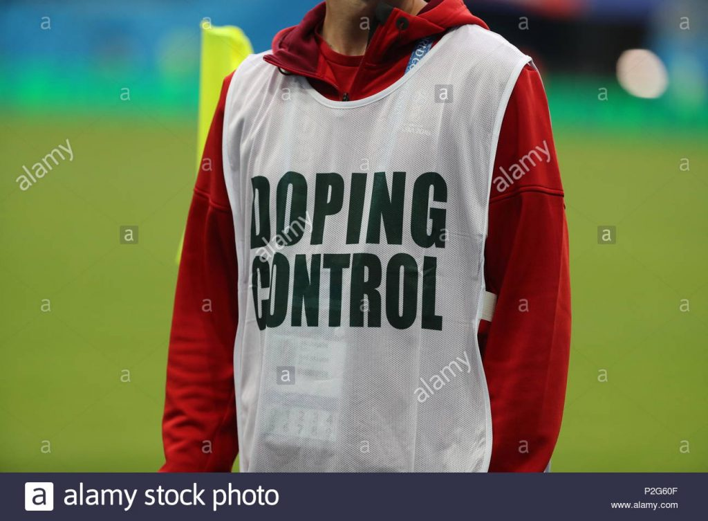 On top of a green background is a person in a red hoodie and white bib. We can only see their chest, no hands, no head. They are wearing a white bib which saying 'Doping Control' in bold, black all caps.