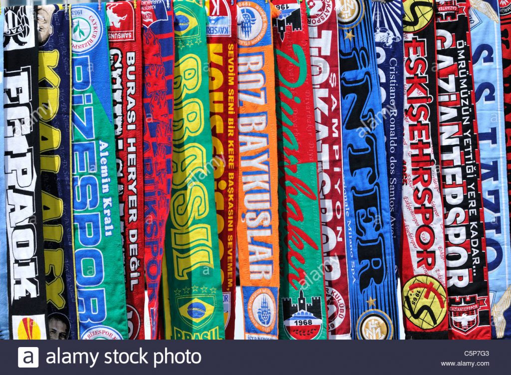 A bright and colourful, candy bar like, collection of football scarves from across the world. They run vertically up the image with all text turned 90 degrees clockwise also.