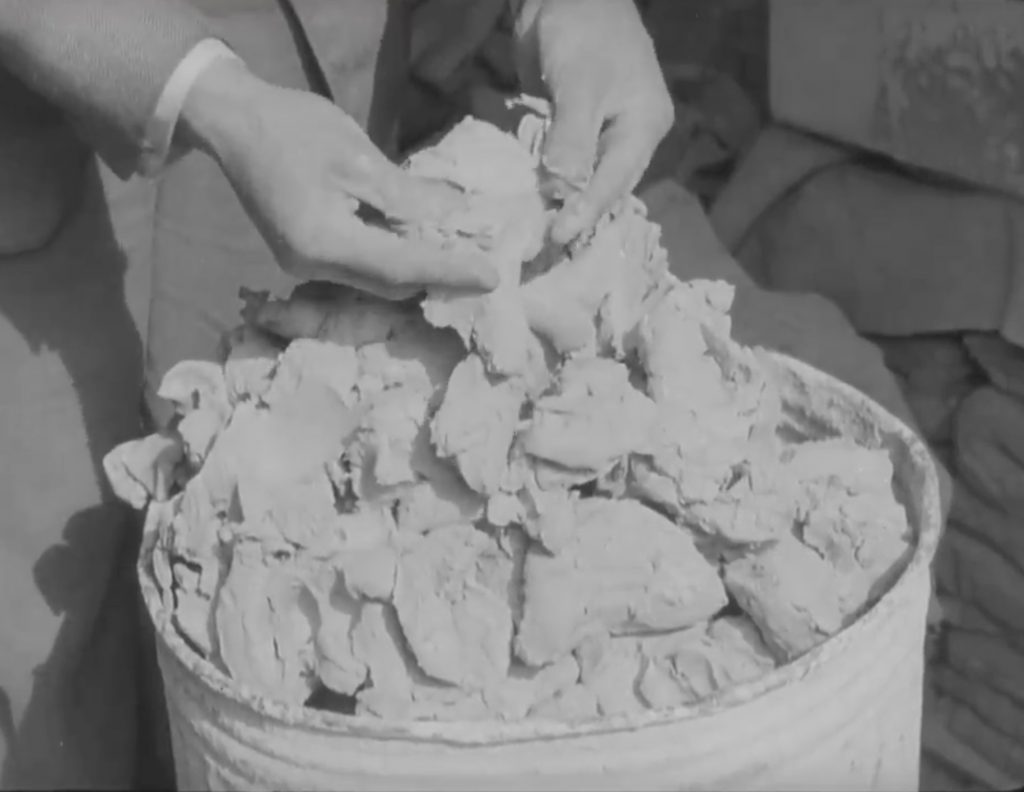 A pair of hands breaking up clay placed inside of a metal bin- the person is wearing suit and is only visible at bottom part and sleeves.
