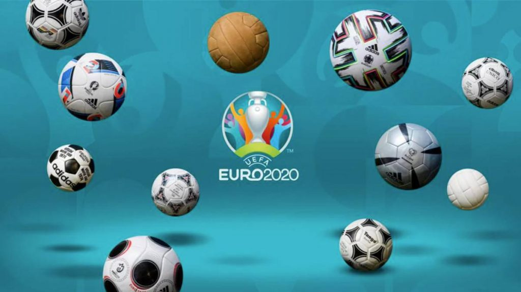 The Euros logo, an aquamarine background with some slightly visible ball graphic design embedded in it, with 3D looking floating footballs scattered across the screen overlaid, all with different patterns and colours on. In the centre is a logo of the trophy and blocky people gathered around it in different bright colours with their arms up. Under it has the white text 'UEFA EURO 2020'