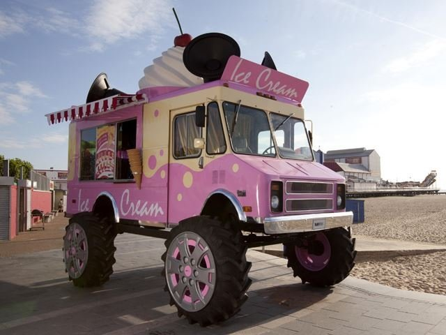 A pink and cream ice cream monster truck with large oversized wheels and a big soft white whip on top with a cherry.