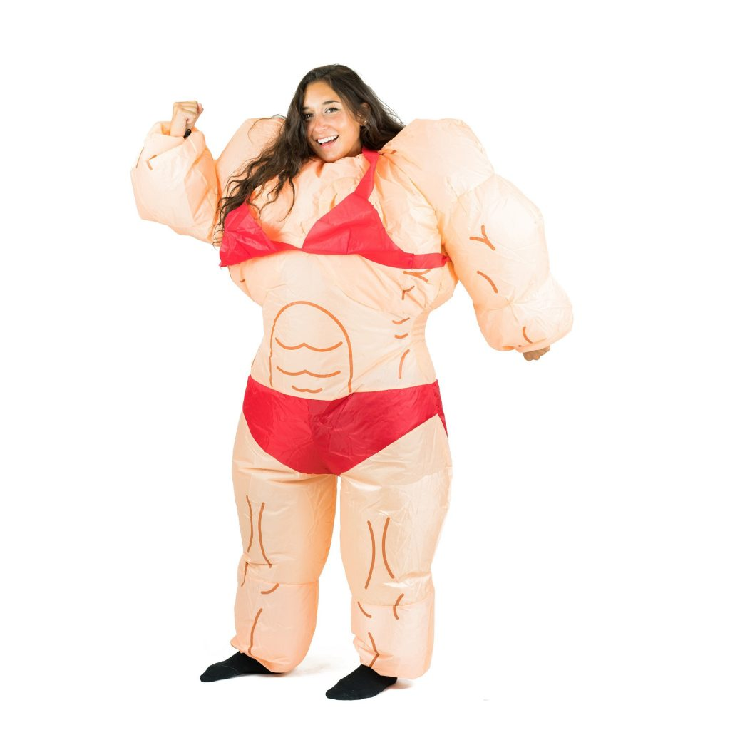 A person with long dark hair and black socks stands there with a wide grin and one fist raised like they're about to pump it in a 'YES' type celebration. This person is wearing a comically large inflatable muscle suit with beige skin, dark brown muscle contours and a red bikini.