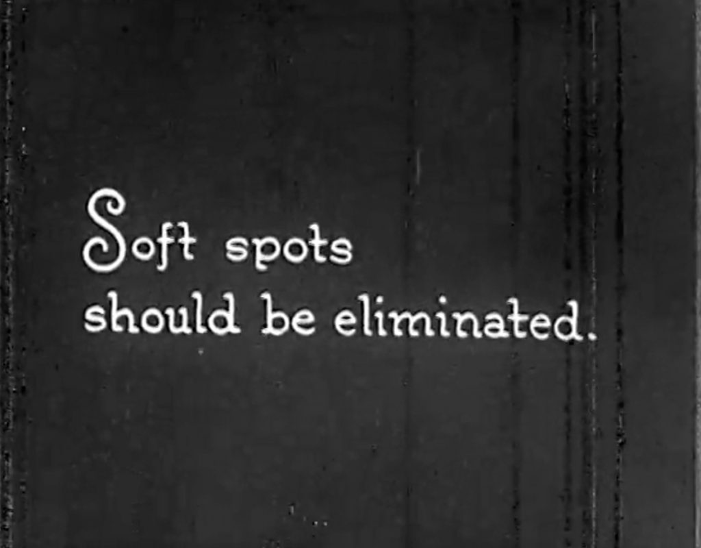 """The intertitle page that says """"Soft spots should be eliminated."""" The background has textured vertical streak as it is an old archive film."""