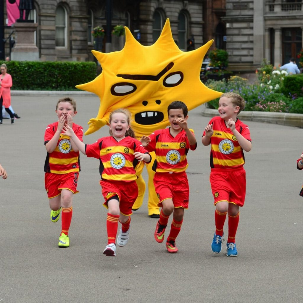 A town square is visible in the background with some planting beds and hedges. In the forefront is a person dressed in yellow trousers and a large mascot top which looks like a giant sunburst with a slightly angry cartoon like facial expression. They are chasing four children who look like they are around eight or nine years old, they look excited and slightly scared to be chased at the same time. They are all wearing red and yellow Partick Thistle football kits. Their arms are flailing up in excitement as they run.
