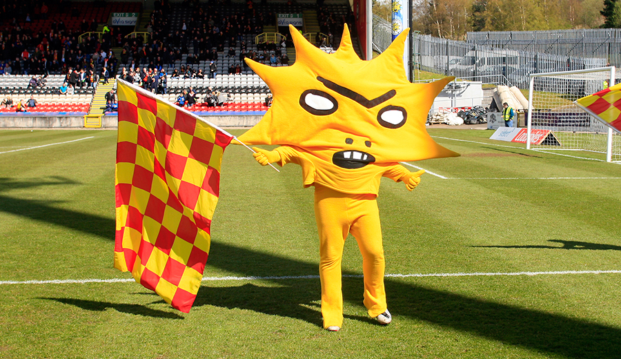 A green football field with a goal net and some fans in the stalls visible in the background. In the forefront is a person dressed in yellow trousers and a large mascot top which looks like a giant sunburst with a slightly angry cartoon like facial expression. It is holding a large red and yellow chequered flag and is giving the thumbs up with it's other hand.