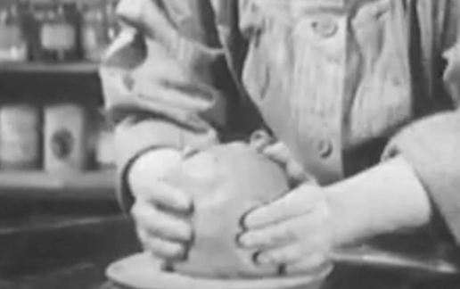 Black and White image of person's hands touching clay on top of wheel to get ready for throwing on the wheel. The person is wearing buttoned up shirt and the image only shows the hands and lower body. Behind the person, there's blurred image of shelves filled with bottles.