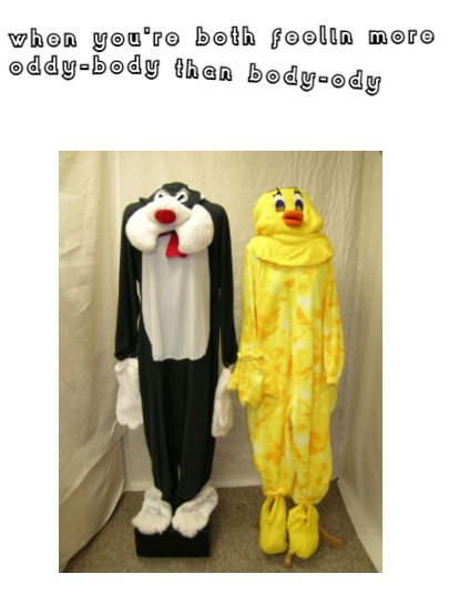 Two costumes hung on stands, one is of Sylvester the cat and the other is Tweety Bird. Sylvester is a black cat with white feet, hands, stomach and cheeks. Tweety is yellow all over with an orange beak and big black eyelashes. They are hung in a small fabric cubicle, the fabric is cream coloured. They look creepy and awkward with no human bodies inside them to fill them out. At the top of the image is some white text with a black background which says 'when you both feel more oddy-body than body-ody'