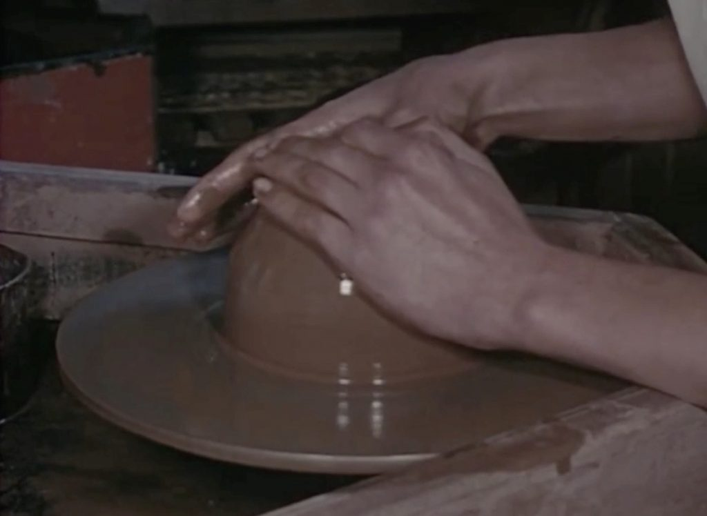 A coloured image of person's both hands shaping the clay which is revolving quickly on a potter's wheel.