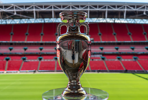 The Euros trophy standing proudly and extremely shiny on a clear glass table in front of the empty stadium. The grass is green and the stands are red in the background.