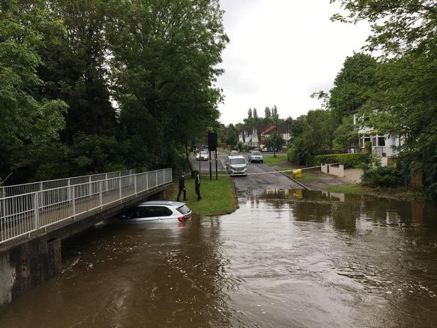 a bmw trapped beneath a bridge and flooding a the river cole