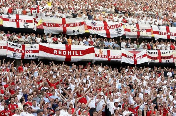 A sea of footy fans, almost all of them have their arms raised up and almost all of them are wearing red and white footy outfits. Many have large England flags which are a white rectangle with a red cross which they have added their hometown names, their own names or their own slogans to such as 'Tommo', 'Bollocks' and 'Redhill', which they have hung off the edge of the stands.