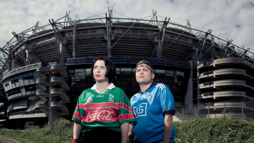Two people stood outside of a large footy stadium shot slightly from below so that the stadium looms over them like an ominous space ship. It's shadowy in front of a cloudy sky. The two people are brightly lit and gaze upwards, both visible from the waist up. The person on the left has a black bob haircut and they are wearing a green and red footy shirt. The person on the right has short brown hair and head band across their forehead and a blue footy shirt with white details. They both have their hands in their pockets, they look slightly pensive like they have seen something in the sky that is about fall down in front of them.