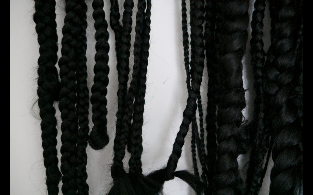 A white background with black braided hair of different thicknesses overlaid and layered over each other.