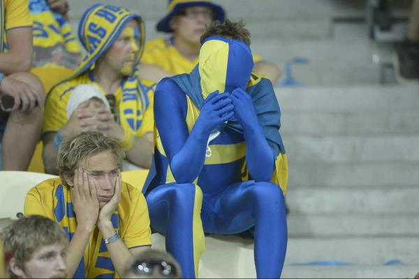 Football fans in blue and yellow sat in the stands of the stadium. Central is someone in a full body blue and yellow morph suit with a flag wrapped around their neck with their head in the hands, all the fans around them look sad and fed up too/