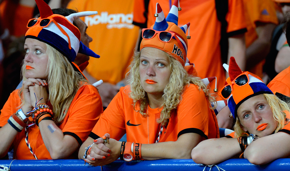 Three football fans all dressed in orange with spiky orange, blue and white hats on with 'Holland' written on them, orange sunglasses on their heads and orange bracelets and lipsticks, leaning on a blue pole at the edge of the stand in the stadium looking sad and fed up.