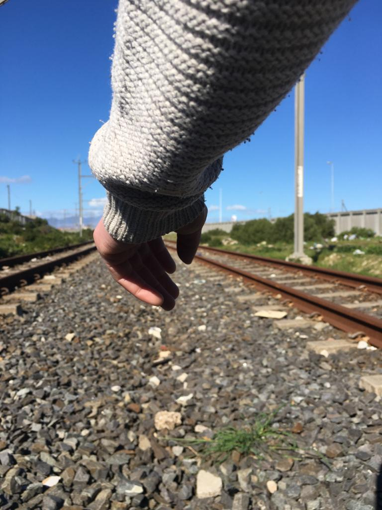 A hand pokes out of a white knitted jumper sleeve. The hand is close to the camera. Ahead of the hand is a rich blue sky, train tracks run either side of the hand, and below are rough grey stones.