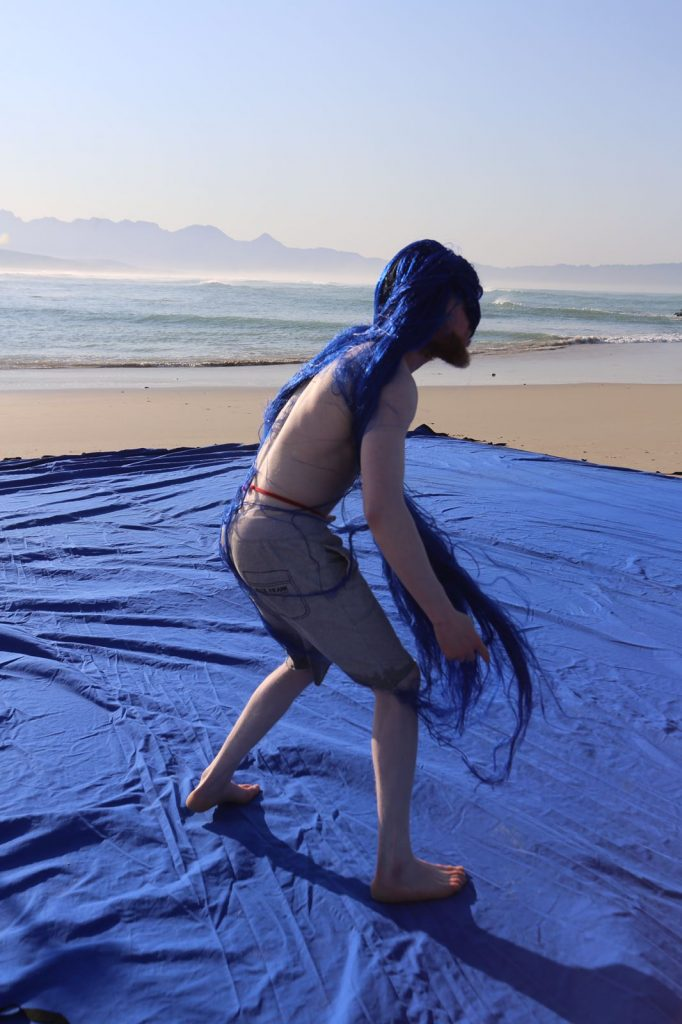 A man stands on a very large widely spread out deep blue blanket, laid over a flat sandy beach. The man wears a dark blue wig, which partially covers his face. He is captured as though in mid-movement, preparing to spin or turn. The sea can be seen behind him in the distance.