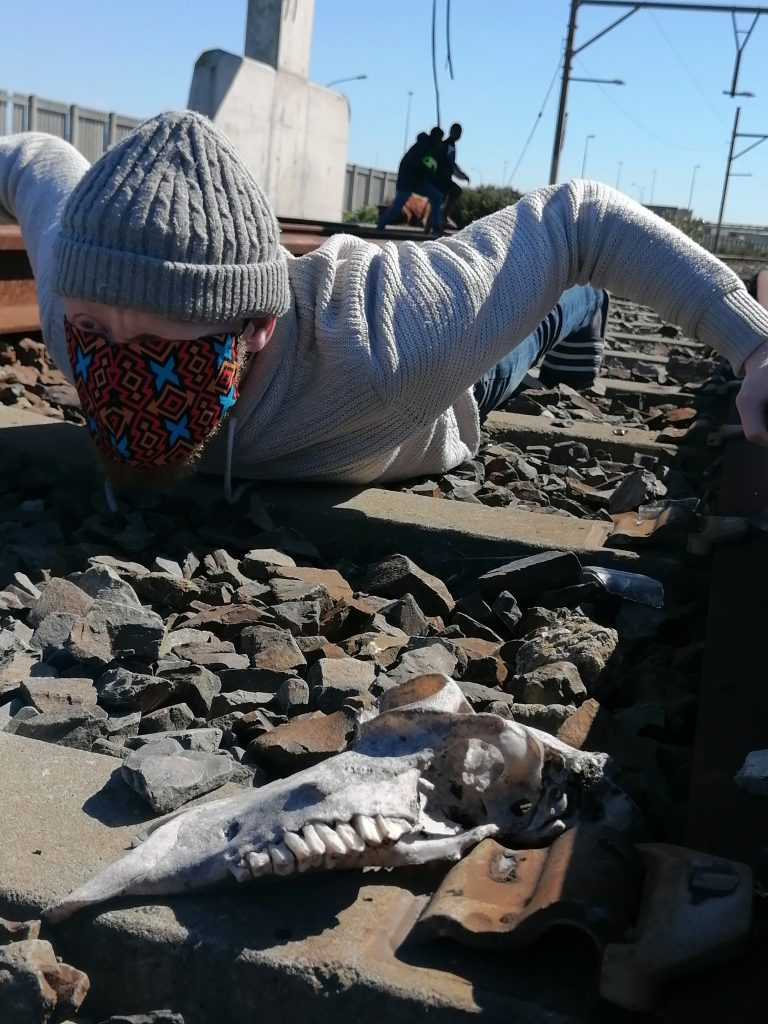 A man lies facing ahead, wearing a colourfully patterned face mask. One eye can be seen peeping out. The man wears a knitted light grey hat and jumper. He is lying face down on train tracks. In front of him is part of an animal skull, with teeth sticking out of the bone.