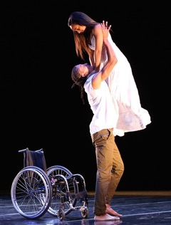 A woman in a long white dress and long dark hair is lifted into the air by a tall man with wearing a white t-shirt and beige chinos. An empty wheelchair is next to them, ignored.