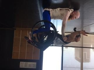 Upside down image of a woman being held in the air in her wheelchair by a man lying on his back.