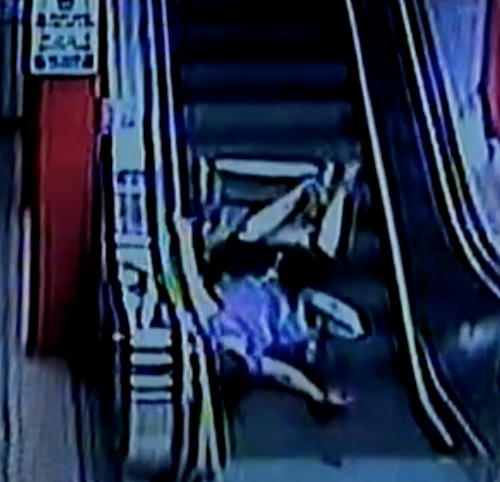 A muffled image in blue and black, a woman in a wheelchair falling backwards down an escalator