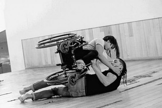 Black and white image of a woman with long dark hair sits horizontally held in her wheelchair in a dance pose. A man lying on the ground holds the woman and her wheelchair above him.